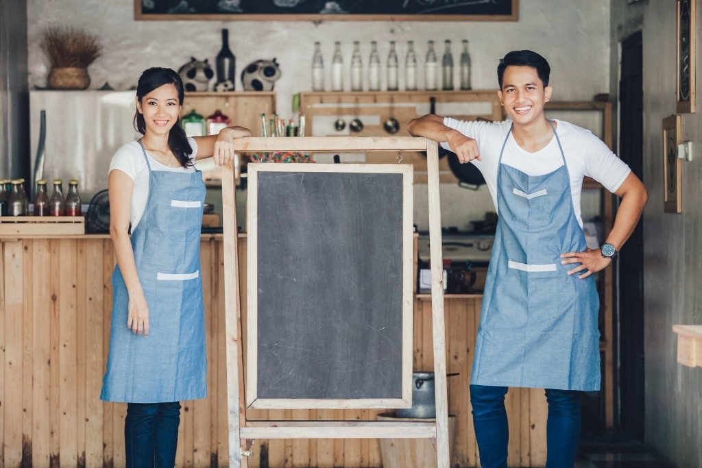 Restaurant owners standing with blank chalkboard