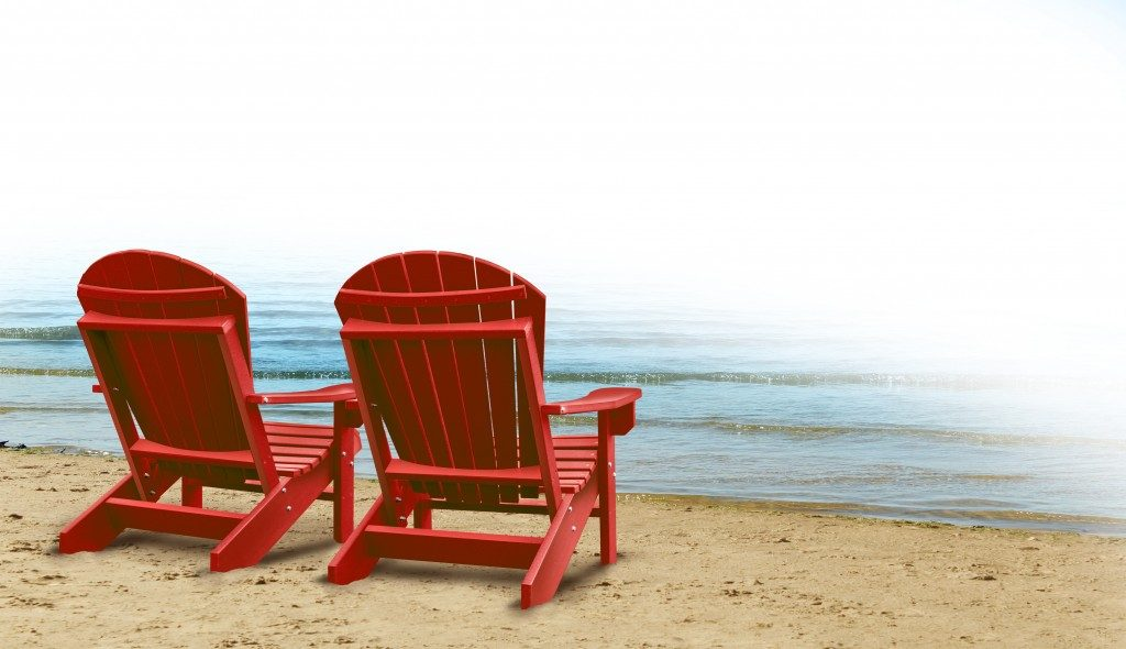 two empty blue adirondack chairs on a tropical sandy beach with ocean view