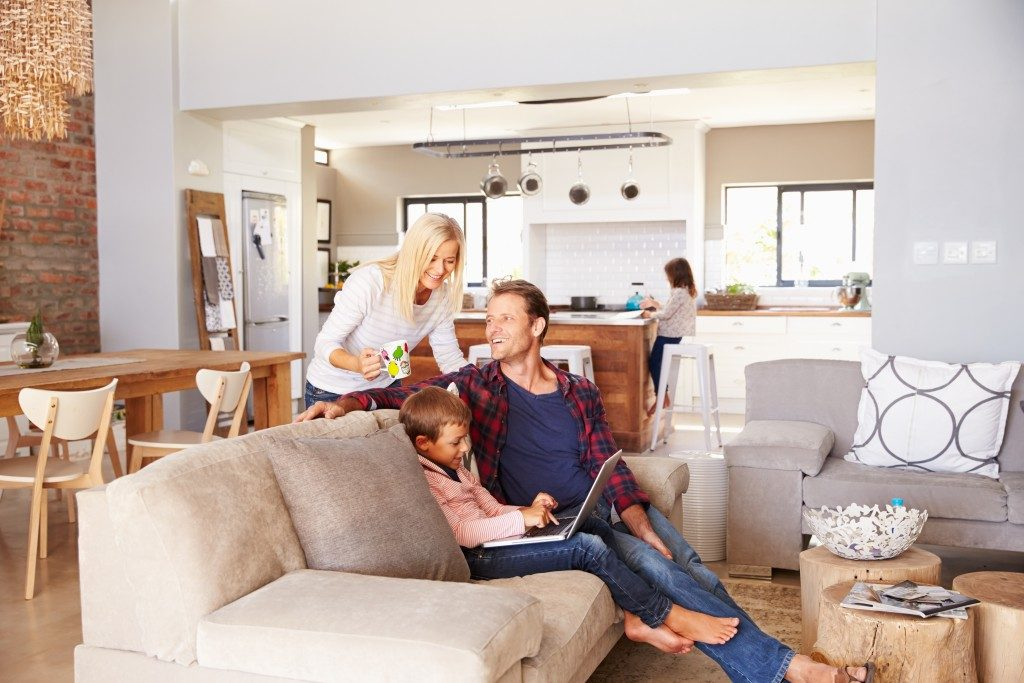 kid with laptop and family members inside the living room
