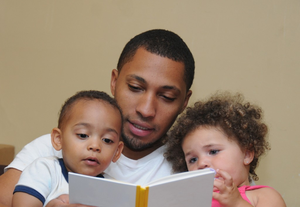 man reading a book to his kids
